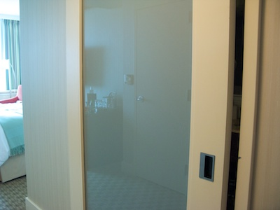 Sliding bathroom door with frosted-glass panel and recessed handle