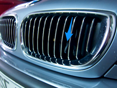 BMW car's front grille with retracted handle somewhat hidden between the grill's fins