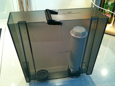 Water tank from a coffee maker with a white filter cartridge mounted in its inside