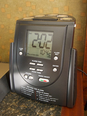 Hilton radio alarm clock on a hotel room nightstand