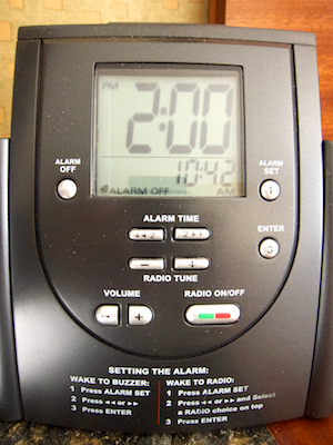 The front panel of the clock with display, control buttons, and printed-on instructions