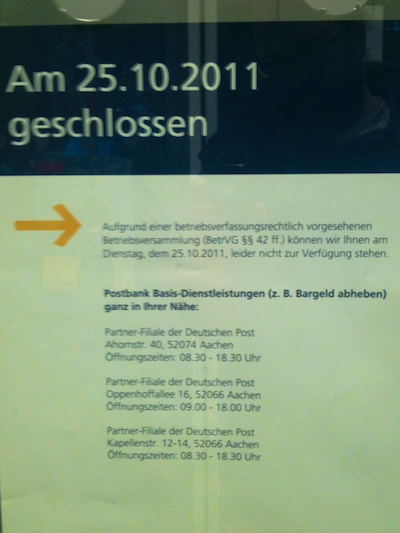 Poster mounted on a door, stating that the post office is closed for the day