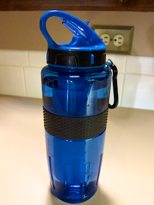 Water bottle sitting on a counter top, showing handle loop, closed spout, and carrying shackle