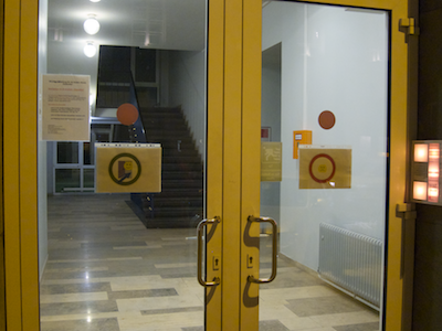 Double-winged glass doorway shown from the outside with a button panel at the right. Both doors have identical handles that are located in the center of the doorway, and the right door's hinges are visible. A circular sign is posted on either door.