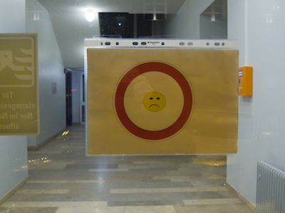Sign on the right-hand door with a red circle, enclosing a frownie.