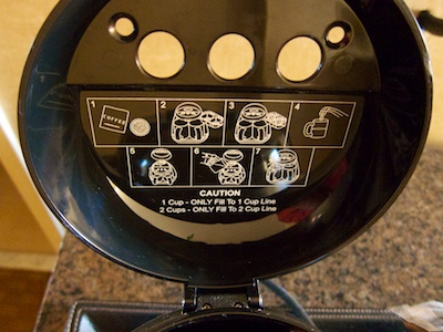 Lid of the coffee maker, lifted up, and displaying iconic brewing instructions on its inside