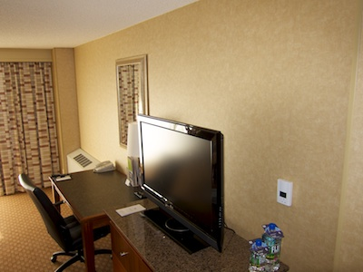 Wall of our hotel room, showing HVAC unit in the far corner and HVAC control panel close by, separated by a desk and TV console
