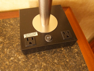 Base of the desk lamp with the lamp's power switch and two 110V power sockets