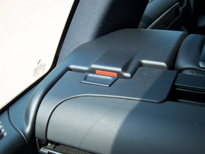 Push button on trunk cover enclosure. The button is down, revealing the red bar on the enclosure's mounting bracket.