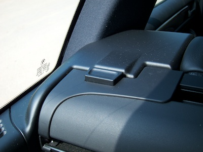 Push button on trunk cover enclosure.