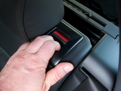 Hand on the rear seat back with two fingers inserted into the unlock handle and pulling the seat back towards the car's front.