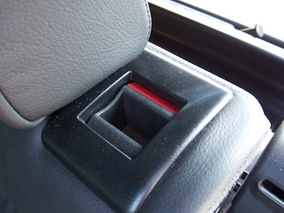 Handle integrated into the rear seat back in the unlocked position, revealing a red area on the handle.