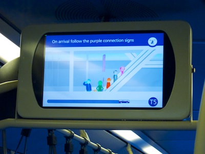A monitor suspended from the bus' roof displays comic-style people on an escalator and states,'On arrival follow the purple connection signs'. The progress bar at the bottom shows that the bus has already gone three quarter of the way to its destination, Terminal five.