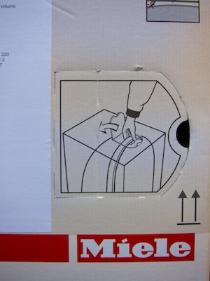 The lid on the side of the box is pre-cut on three of its four sides and bears a graphic that illustrates how to open it, and what to grab on the inside.