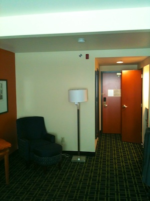 A tall floor lamp's screen at the other end of the room blocks the view of the thermostat mounted to the wall.