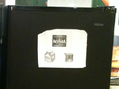 A sheet of paper is affixed to the fridge with the opaque door, showing the Activia brand symbol, a generic milk carton sketch, and an Activia yoghurt cup. All in glorious gray-and-white, and rather fuzzy at the edges.