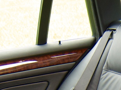 Inside view of a car's rear door with lock pin sticking out from the top of the inside door cover.
