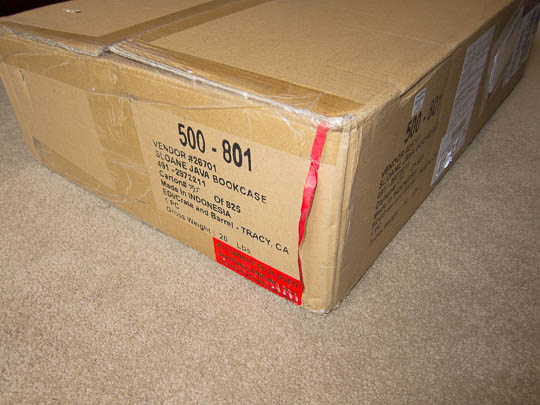 The large carton containing the shelves' parts. The red ribbon is clearly visible on the cardboard.