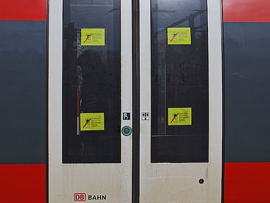 Train door showing four out-of-order warnings placed in the door's windows.
