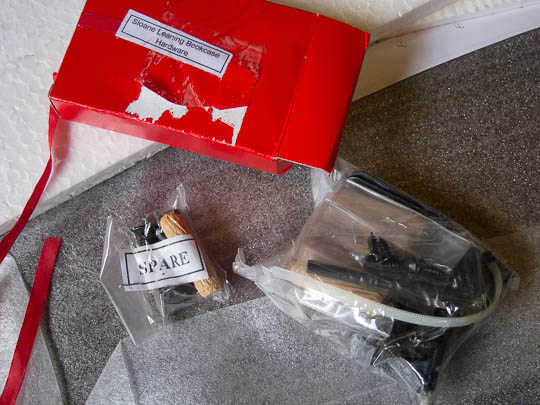 Two plastic bags contain numerous mounting hardware parts like screws, etc. These bags are contained in the small, red cardboard box that the ribbon is attached to.