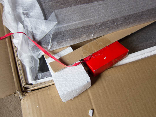The small, red cardboard box is attached to packaging elements inside the large carton. The red ribbon attaches to that small box.